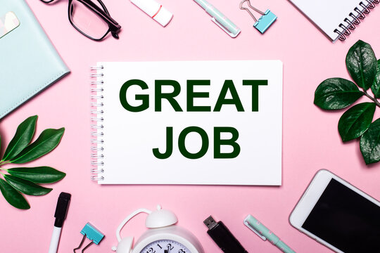 GREAT JOB is written in a white notebook on a pink background surrounded by business accessories and green leaves.