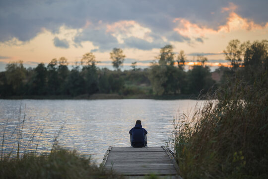 One adult young man sitting on edge of footbridge and staring at lake and cloudy sunset sky. Thinking about life. Spending time alone in nature. Peaceful atmosphere. Back view.