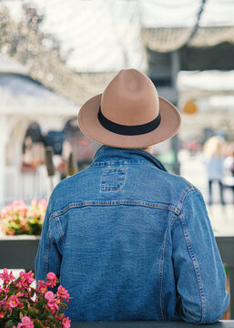 A man in a denim jacket and a hat stands with his back and looks at the busy street. Tourism concept, summer vacation.