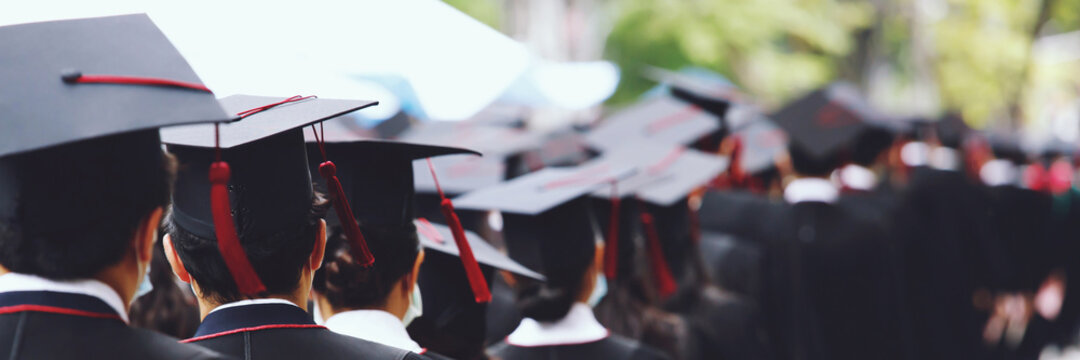 Group of Graduates during commencement stand in row. Concept education congratulation in University. Graduation Ceremony. copy space banner.