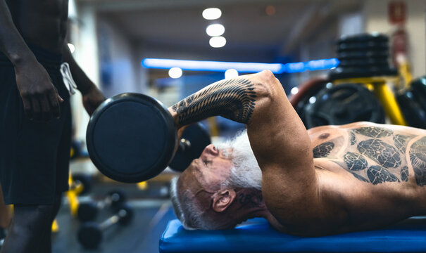 Senior fit man weight lifting with personal trainer in gym sport club - Mature bodybuilder doing workout session - Bodybuilding and fitness concept