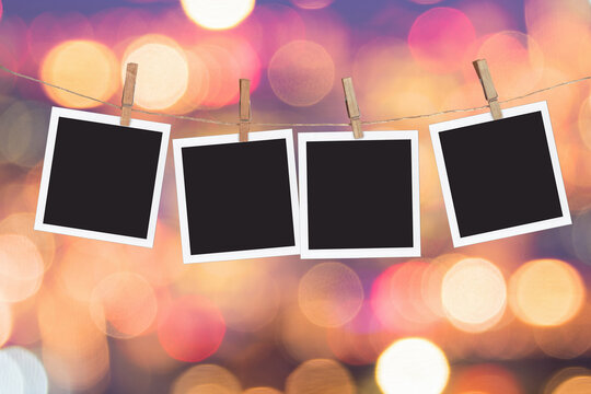 Four blank instant photo frames hanging on a rope, on holiday lights bokeh background