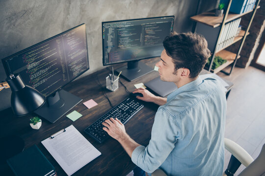 Top above high angle view portrait of his he nice attractive focused skilled geek guy typing bug track report cyberspace security at modern industrial interior style concrete wall work place station