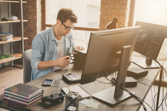 Portrait of his he nice attractive busy skilled experienced focused geek guy repairing part pc cpu hard disk drive handiwork at modern loft brick interior style work place station indoors