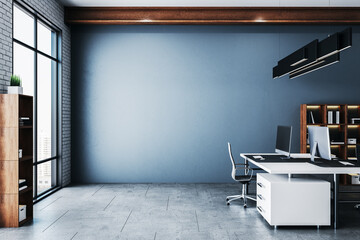 Coworking office in a loft style interior with blank blue wall.