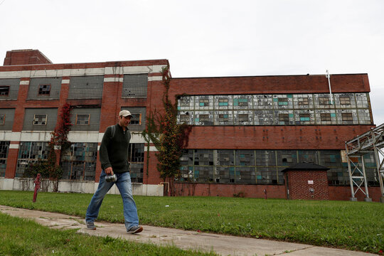 A man walks past an abandoned Packard Electric Company building in Warren, Ohio