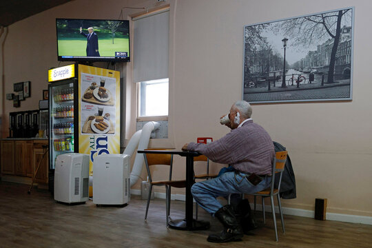 A diner watches a news report about U.S. President Donald Trump in Bangor