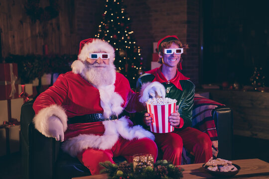Photo portrait of santa claus and elf eating popcorn watching movie on sofa in 3d glasses