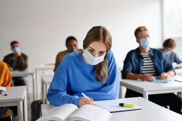Young students with face masks at desks at college or university, coronavirus concept.