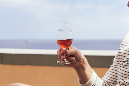Tasting of Madeira wine in man's hands, ocean on the background