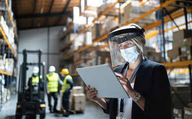 Manager with protective shield uisng tablet indoors in warehouse, coronavirus concept.