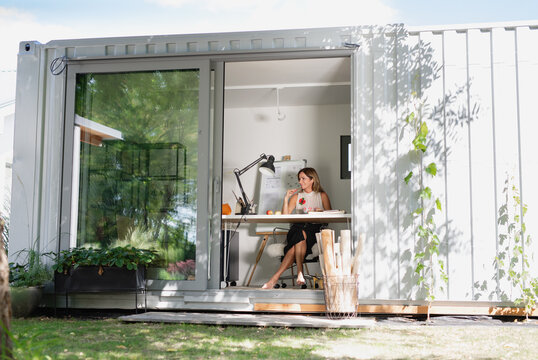 Mature woman working indoors in home office in container house in backyard.