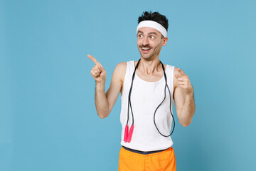 Excited young man with thin skinny body sportsman in white headband shirt shorts stand with skipping rope over neck pointing index fingers aside isolated on blue background. Workout gym sport concept.