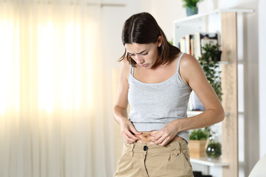 Woman worried about body fat touching her belly