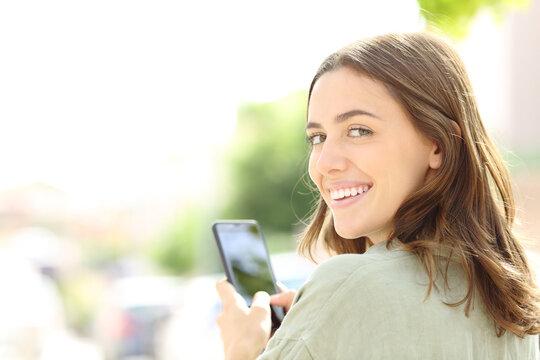 Happy woman using phone smiling at camera
