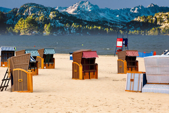 Bungalows sun protection on the beach for rent in summer holiday and snowy mountains in the background