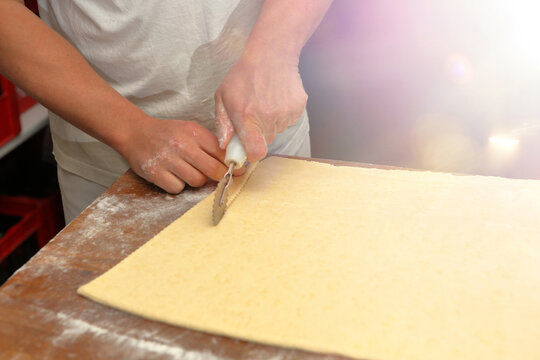 Baker cuts the dough for croissants and empty space for text