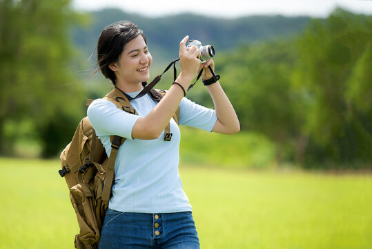Asian young woman holding camera and standing in the jungle adventure.  Tourism for destination and leisure trips for education and relax in nature park.  Travel vacations and Lifestyle Concept