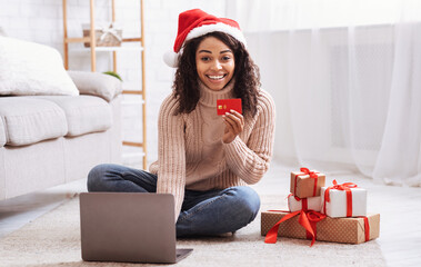 Xmas Shopping. Black lady using laptop holding credit card