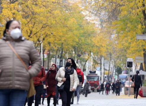 People walk along a shopping street in Vienna