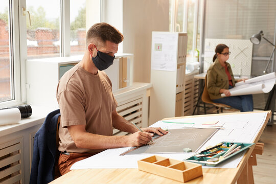 Side view portrait of mature bearded architect wearing mask while sitting at drawing desk in sunlight, copy space