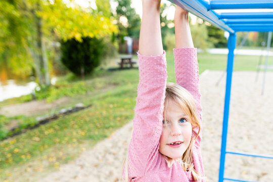 Happy young girl on monkey bars at a playground
