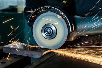 Hand cutting metal in the workshop with sparks.