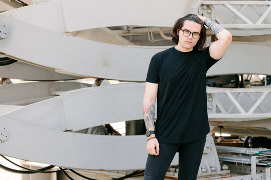 Hipster handsome male model with glasses wearing black blank t-shirt and black jeans with space for your logo or design in casual urban style