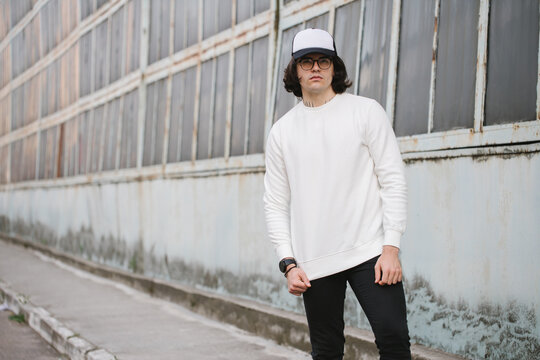 Man wearing white sweatshirt and a black hat standing over gray background. Sweatshirt or hoodie for mock up, logo designs or design prints with with free space.