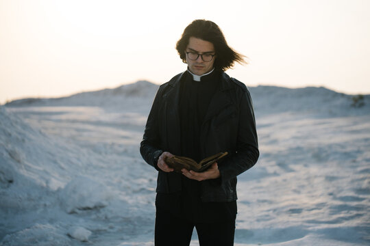 Young priest portrait outside at sunset. He is wearig eye glasses and roman collar shirt and a leather jacket.