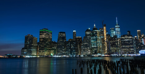 Fotobehang - Night photo of glowing skyscrapers and a view of Manhattan Bay. Long duration. Panoramic photo. The splendor of the city at night.
