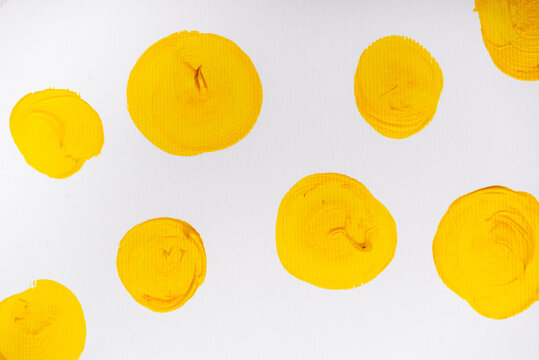 top view of abstract colorful yellow painted circles on white background