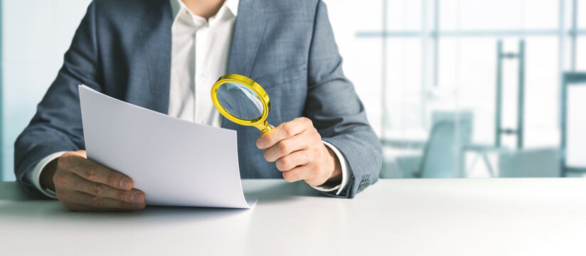 businessman or tax inspector analyzing document with magnifying glass in office. business financial audit concept. copy space