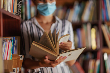 Closeup of attractive college girl standing in library with face mask on and reading a book....
