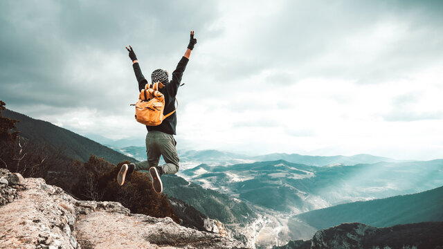 Successful hiker man jumping on the top of the mountain - Successful, business and sport concept.