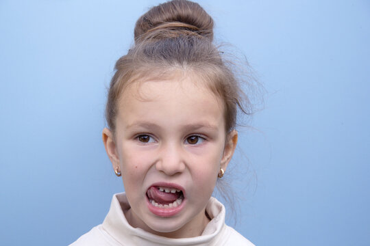 A light-skinned girl holds her tongue on her teeth to to train her speech. Blue background