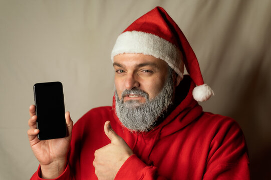 santa claus shows his cellphone and a thumb up