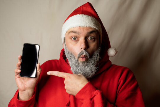 santa claus points to his cell phone in surprise