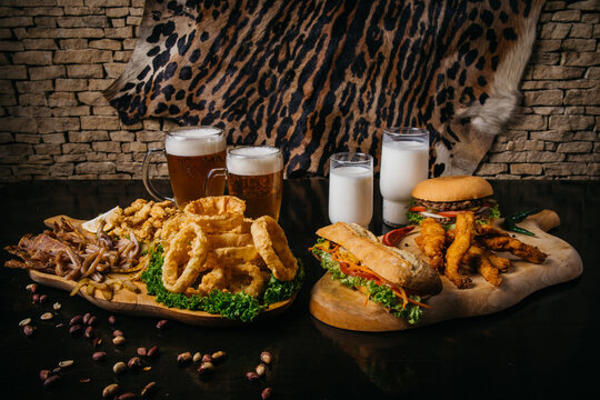 beer and food party with meat and drinks burgers sandwiches and onion rings. High quality photo