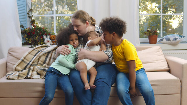Portrait of caucasian mother with mixed race children sitting on couch in living room