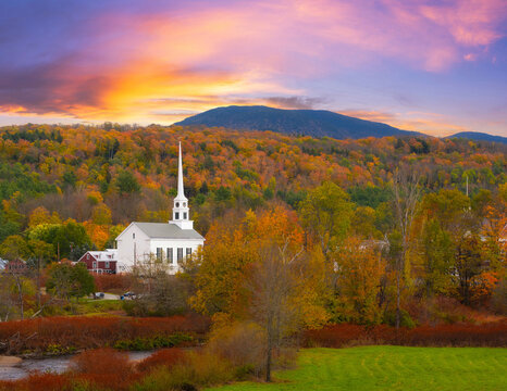 Colorful sky and fall foliage surrounding Stowe Church in Vermont