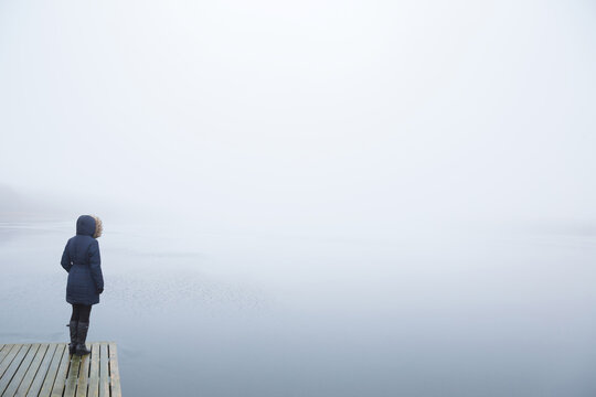 Young adult woman standing alone on edge of footbridge and staring at lake. Mist over water. Foggy air. Early chilly morning. Peaceful atmosphere. Empty place for text, quote or sayings. Back view.
