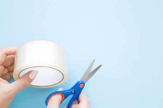 Young woman hands holding transparent scotch roll and scissors. Light pastel blue background. Closeup. Empty place for text. Top down view.