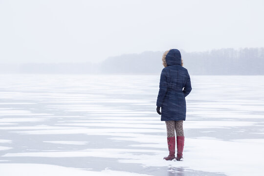 One young adult woman in snow blizzard standing alone on lake ice.  Cold atmosphere. Foggy air. Winter concept. Back view.
