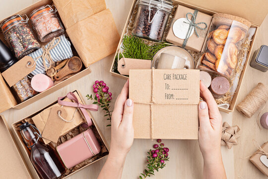 Preparing care package, seasonal gift box with coffee, cookies, candles, spices and cups