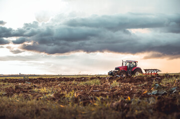 Tractor plowing the fields in the countryside by sunset. Agricultural tractor plowing the field. Red Tractor with plow. Sunset over the autumn field.