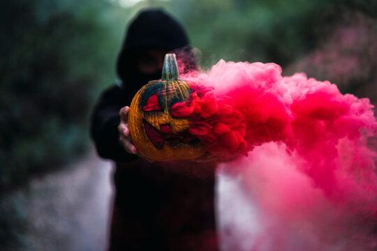 Chico joven con mascarilla por covid 19 con calabaza de halloween con humo de color