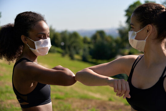 Two diverse african and indian fit ladies friends wear face masks give elbow bump. Sporty young women non-contact greeting together outdoor meeting for fitness training or running outside. Closeup.