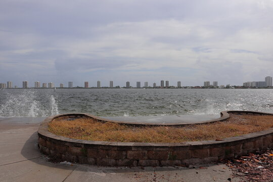 Waves crashing on the seawall looking east towards the singer island skyline.