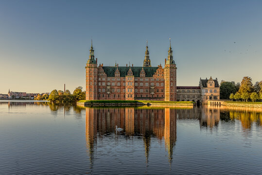 Frederiksborg castle glimmers in the sunshine and is reflected in the mirror-shiny lake